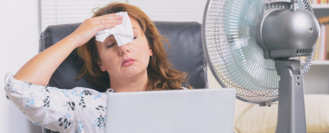 Woman tries to cool down in hot office