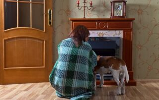 woman in blanket with dog near a fireplace