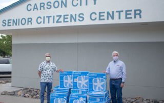 Dirk Roper and Michael Salogga stand in front of the Carson City senior Center with stacks of 24 box fans